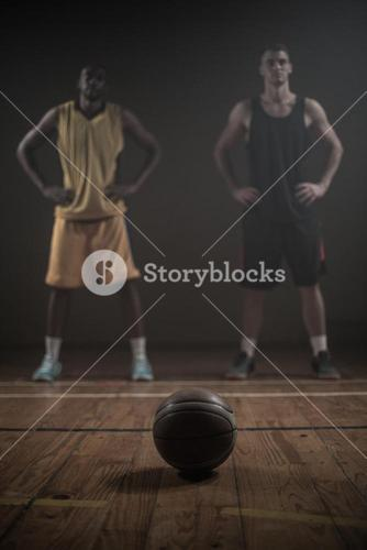 Basketball players posing with hands on hips behind a ball