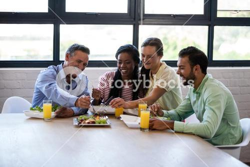 Smiling team of  business people having lunch