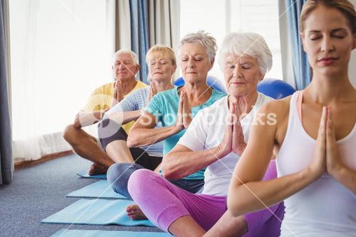 Front view of seniors relaxing with fitness instructor