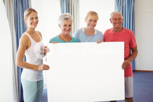 Seniors and fitness instructor holding a blank paper