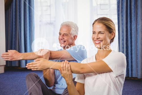Portrait of fitness instructor and senior stretching their arms
