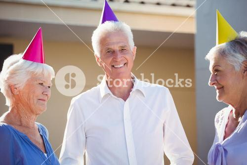 Portrait of seniors smiling with party hats on head