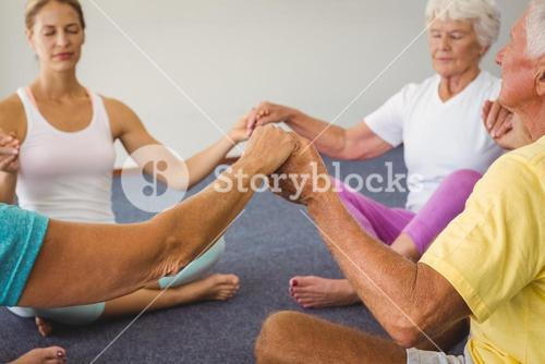 Concentrated seniors holding hands together in circle