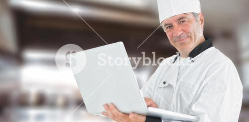 Composite image of friendly chef holding a laptop