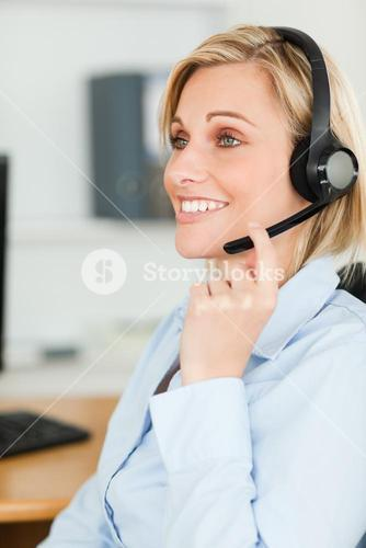 Portrait of a smiling businesswoman with headset looking elsewhere