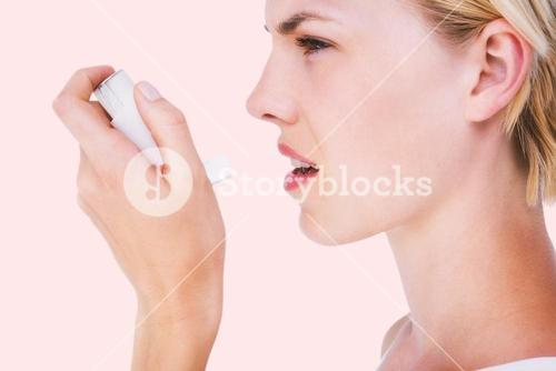 Composite image of asthmatic pretty blonde woman using inhaler