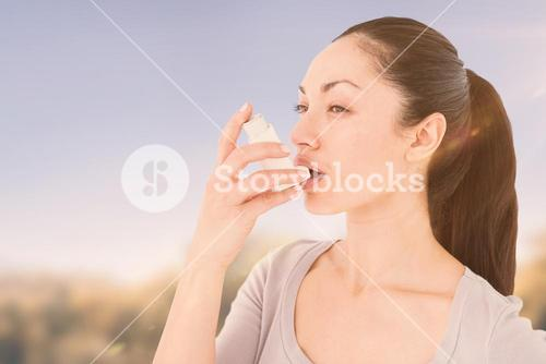 Composite image of asthmatic pretty brunette using inhaler