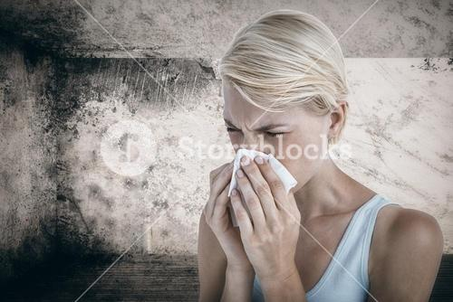 Composite image of portrait of woman blowing her nose