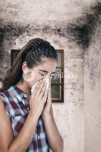 Composite image of sick woman sneezing in a tissue