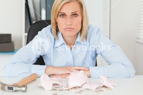 Sad woman sitting in front of an shattered piggy bank with less in than expected