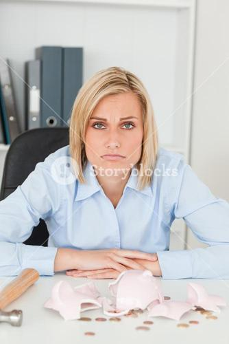 Sulking woman sitting in front of an shattered piggy bank looking into camera