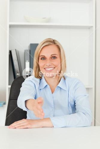 Smiling blonde businesswoman giving hand