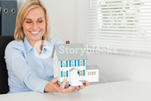 Smiling woman showing model house