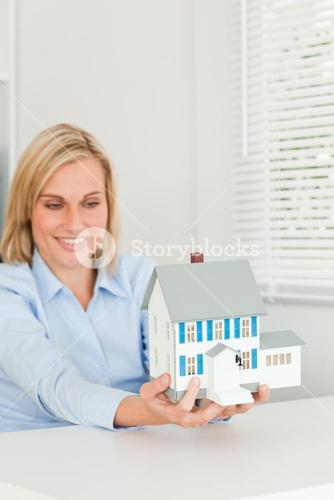 Smiling businesswoman showing model house