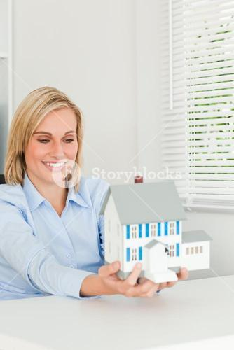Gorgeous businesswoman showing model house looking at it