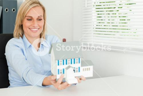 Gorgeous businesswoman presenting model house looking at it