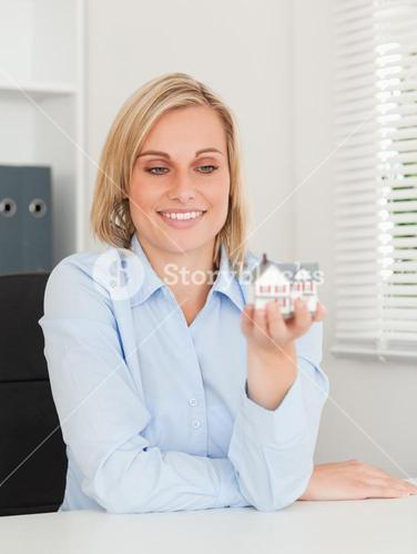 Gorgeous blonde businesswoman showing miniature house looking at it