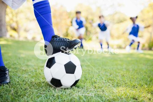 Close up view of balloon under football boots against children playing background