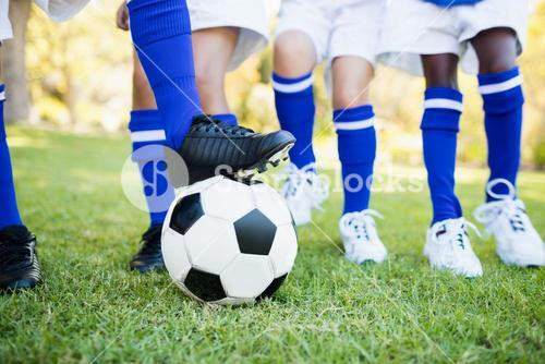 Close up view of balloon under football boots with children playing