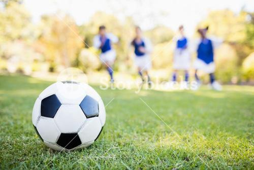 Extreme close up view of soccer balloon against children background