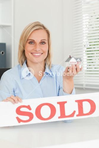 Gorgeous blonde businesswoman showing miniature house and SOLD sign looking into camera