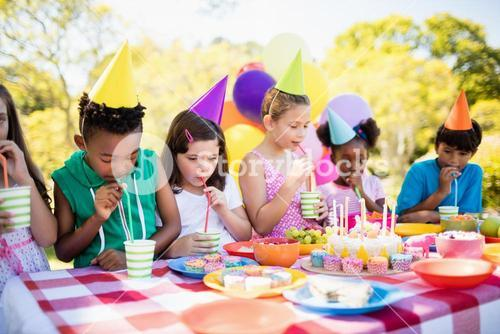 Group of children drinking with straw during a birthday party