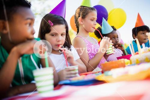 Children drinking with a straw during a birthday party