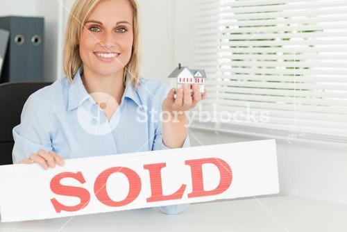 Blonde businesswoman showing miniature house and SOLD sign looking into camera