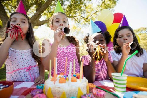 Children breathing out in a birthday trumpets during a birthday party
