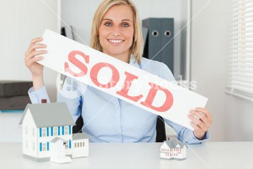Blonde businesswoman showing SOLD sign looking into camera