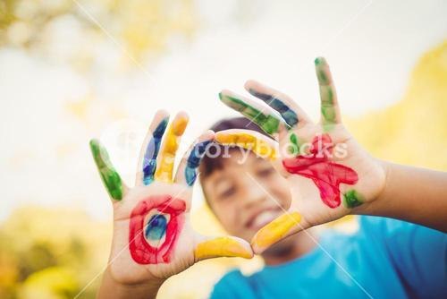 Boy making a circle to the camera with his hands painted