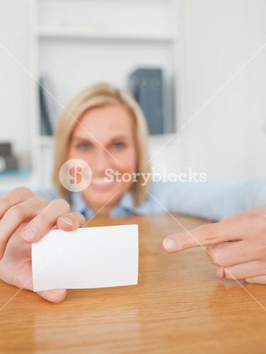 Blonde smiling businesswoman pointing at a card crouching behind her desk