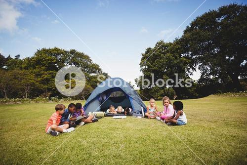 Smiling kids lying and reading in the tent together