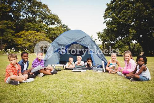 Smiling kids posing in the tent together during a sunny day