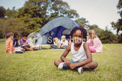 Smiling kid posing on grass during a sunny day with other children