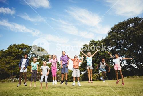 Smiling kids jumping together during a sunny day