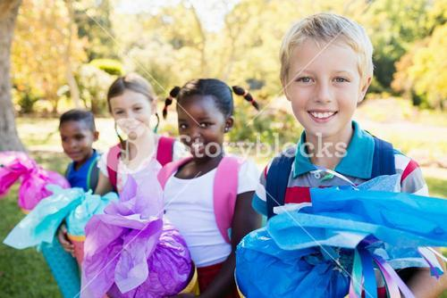 Kids posing with their gift surprise during a sunny day