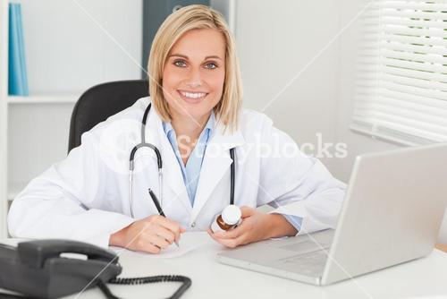 Doctor writing something down holding medicine looks into camera