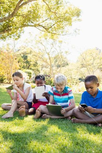 Kids using technology during a sunny day