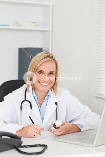 Doctor writing something down while holding medicine looks into camera