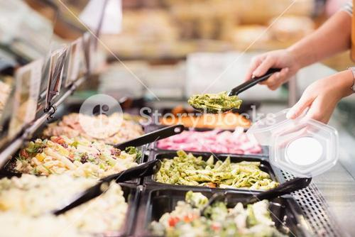 Close up view of hands picking prepared meals