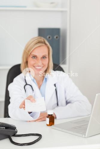 Smiling doctor holding prescription looks into camera