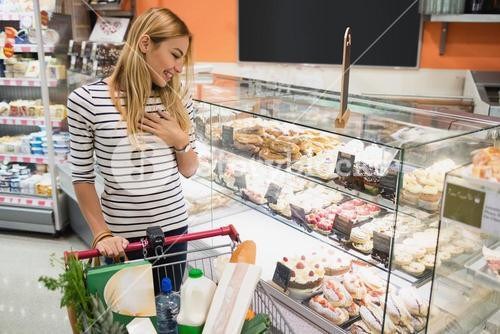 Smiling blonde woman looking at desserts