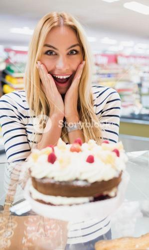 Happy woman with mouth open in front of cake