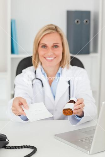 Smiling blonde doctor holding prescription and medicine looks into camera