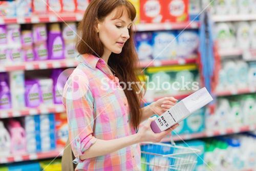 Profile view of woman with shopping basket holding product