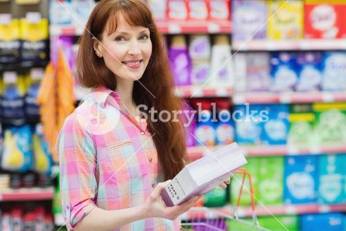 Portrait of woman with shopping basket holding product