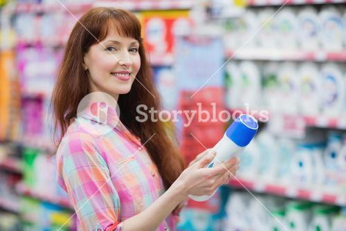 Beautiful woman posing with detergent
