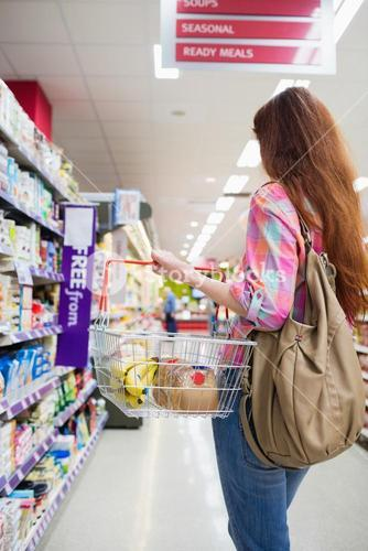 Woman doing grocery shopping with shopping basket