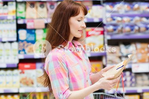 Concentrated woman choosing carefully a product